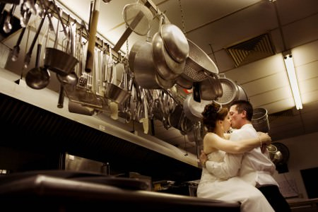 An image of a bride in her white gown sitting on the stainless steel counter inside the kitchen of Todaro's Party Center with her groom embracing her in a kiss while the silver pots and utensils hang above their heads.