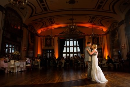An image of a bride in her white lace gown slow dancing with the groom in a grey tuxedo in the lower right half of the photo on the dark wooden floor of the Tudor Arms while round tables surround the dance floor in the background of the dark colored photo and orange uplight add a glow of color on the back wall.