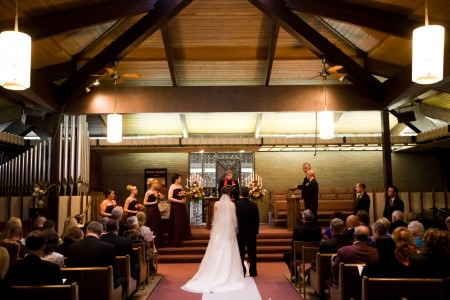 A bride and groom standing holding hands in front of the officiant at the altar of the Unitarian Univeralist church with with wedding party on the steps and a candelabras lit with floral bouquets.
