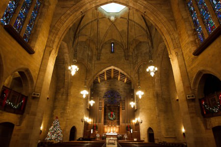 A image of inside the sanctuary of University Circle United Methodist church looking up the at stone arched high vaulted ceiling with a circular skylight while facing the altar with the wooden back wall and the sanctuary has been decorated with Christmas trees and wreaths with red ribbons and white lights for Christmas.