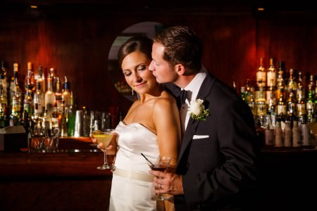 A waist high image of a bride in her white strapless satin gown is leaning with her back to her groom's chest who is dressed in his black tuxedo with black bowtie and a white rose pinned to his lapel while they both are up against the counter top of a bar at the Velvet Tango Room holding martini cocktails with liquor bottles in the background against a red colored wooden wall.