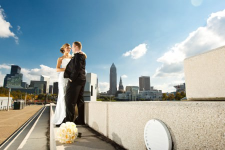 A picture taken from ankle height looking up at a bride and groom standing on a cement sidewalk where the bride is in her white strapless dressing turned toward the groom in his black tuxedo with her left arm up around his shoulder on a bright sunny day with the Cleveland skyline in background and the bride's white rose bouquet rests on the sidewalk in the foreground.