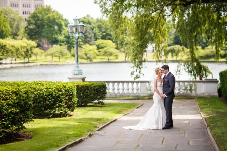 "A picture of a bride and groom standing on an ""L"" shaped stone pathway holding hands with their heads tipped together and and a white cement fence behind them with a lake beyond the fence and green grass with green shrubs in the left of the photo."