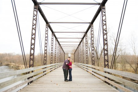 A picture of an engaged couple hugging on a wooden bridge with metal beams on a grey overcast fall day in Zoar, OH.