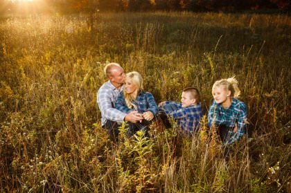 Portrait of a family of four in a grassy field during their Akron portrait session with Genevieve Nisly Photography.