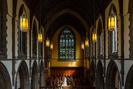 A view from the balcony of the Amasa Stone Chapel in Cleveland, Ohio overlooking a bride and groom standing at the altar with their wedding party and the ornate stained glass window on a yellow wall with arched stone ceiling and golden lights hanging down.