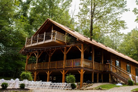 An image of the outside of the Grand Barn at the Mohicans with cafe lights hanging over the patio with white wooden chairs set for a wedding ceremony and the wooden building set back up against the patio.