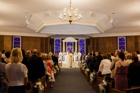 A picture taken down the center aisle of a bride and groom standing at the altar in front of the priest as the wedding guests stand up in their wooden pews in the sanctuary of St. Francis Church white it's dark wood walls with purple stained glass windows that lead up to a white ceiling with a six-sided trayed ceiling.