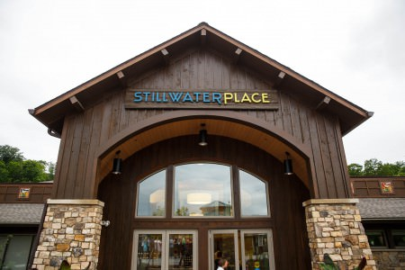 An image of the outside of the Stillwater Place looking up from the ground towards the top front of the building with the stone pillars leading to the dark wooden walls of the overhang with the blue and yellow lettered sign just above the arch on grey overcast day.