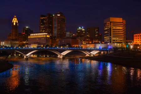 A beautiful picture taken at night of the city of Columbus where the river is in the lower half of the photo with a bridge running through the middle of the picture with blue circular pathway lights all being reflected in the river under a midnight blue sky.