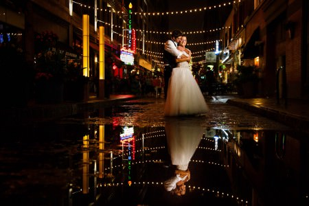 A stunning image of a groom embracing his bride from behind and resting cheek to cheek in the middle of East 4th Street in Downtown Cleveland after a rainy night where the strung cafe lights and bright colored signs are reflected along with the couple's image in a puddle on the street.