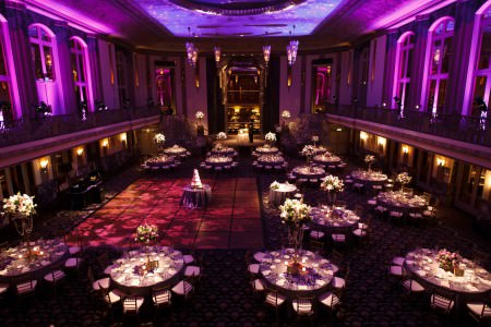A bird's-eye view of the ballroom at the Hilton Cincinnati Netherland Plaza set for a wedding reception with rounded tables surrounding the dance floor with tall floral arrangements and purple lighting shining on the second story balcony of this French Art Deco style ballroom.