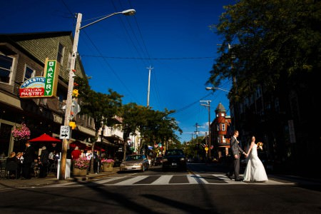 A bride leading the way across a crosswalk in Little Italy with her arm stretched back holding her grooms hand and looking over her shoulder on the corner of a street in Little Italy near Cleveland, Ohio on a bright blue sky day.