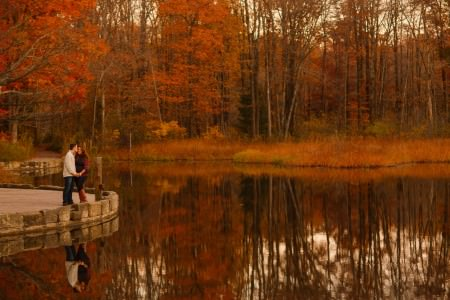 A stunning image taken of an engaged couple taken during the peak of the fall foliage at the North Chagrin Reservation in Ohio where they are standing in the far left side of the photo on a cement path that is up against a small lake with trees on the other side in brilliant reds and oranges and everything is reflected in the water.