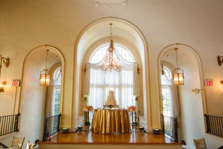 A picture of a wall with arches cut into it to surround three arched windows that each have a light fixture hanging from the center of the arch with the middle window displaying a very ornate crystal chandelier with a round table under it draped in a gold tablecloth holding a three tiered white wedding cake.