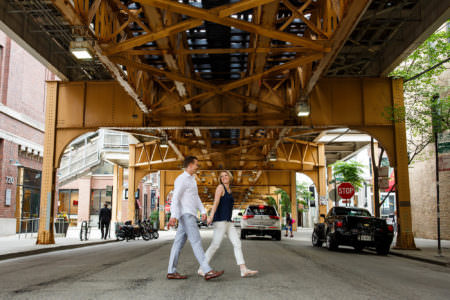 Engaged couple walk hand-in-hand under the brown line in Chicago.