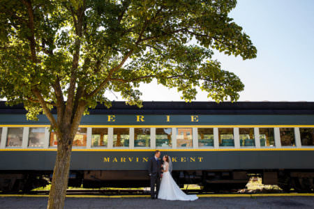 A photo of a bride and groom standing at the bottom center of the photo where the bride is holding onto the groom's arm as they look into each other's eyes in front of a green and yellow train sitting on train tracks on a bright sunny day with a small tree trunk in the left foreground with green leaves at the top of the photo taken in downtown Kent, Ohio.