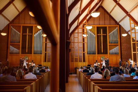 A mirrored image split down the center taken of the sanctuary of the United Church of Christ where the right side of the photo shows the brick and wood wall of the front of the church with the silver organ pipes and tall cross hanging with a bride and groom facing each other and holding hands with guests sitting in wooden pews watching the ceremony and the left side of the picture is the mirrored image.