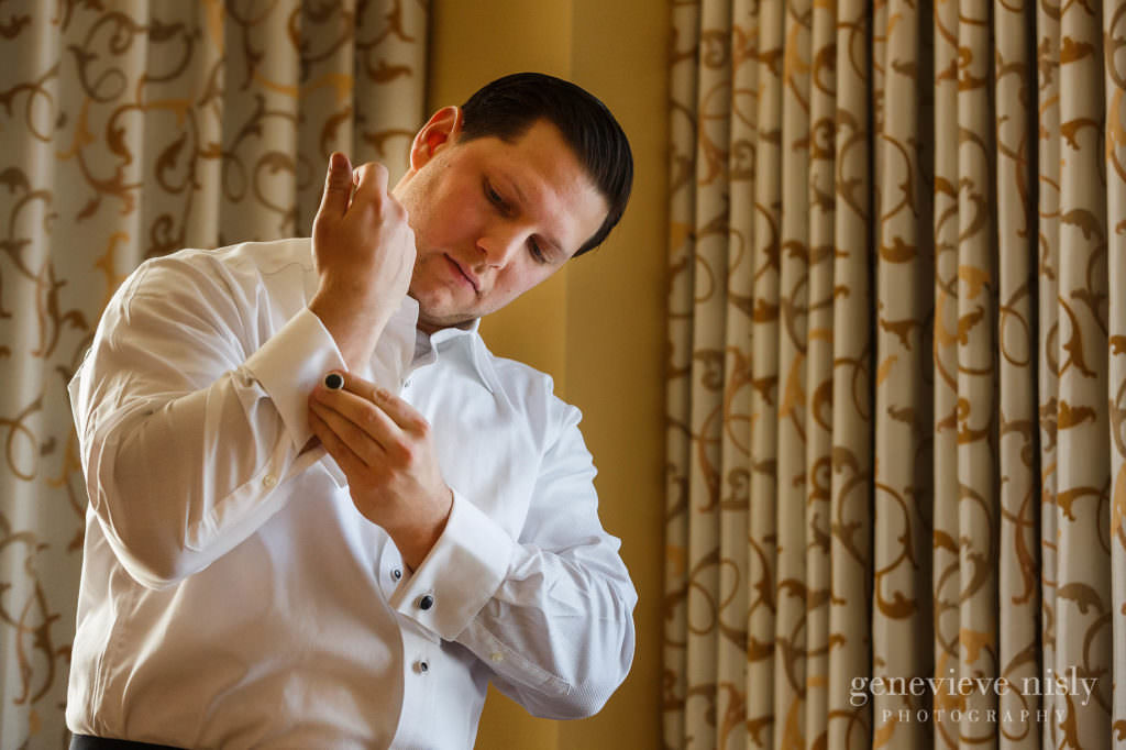 Groom fastens cufflink while preparing for his wedding at the Ritz Carlton in Cleveland.