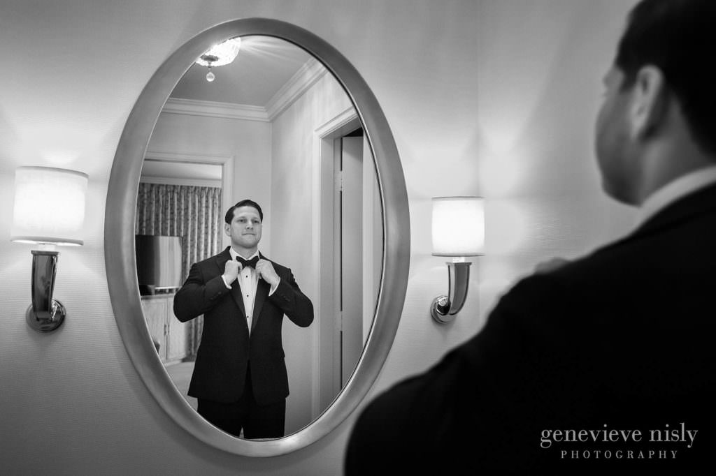 Groom adjusting his bow time in a mirror.