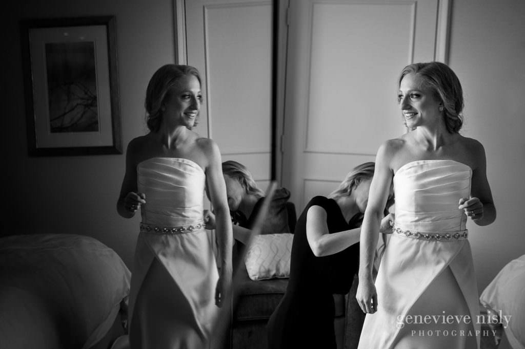 Bride getting into her wedding dress on her wedding day.