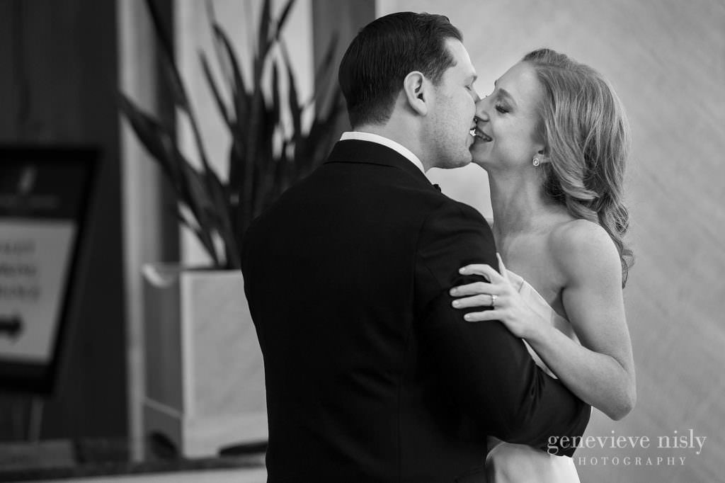 Bride and groom kissing with a smile on her face.