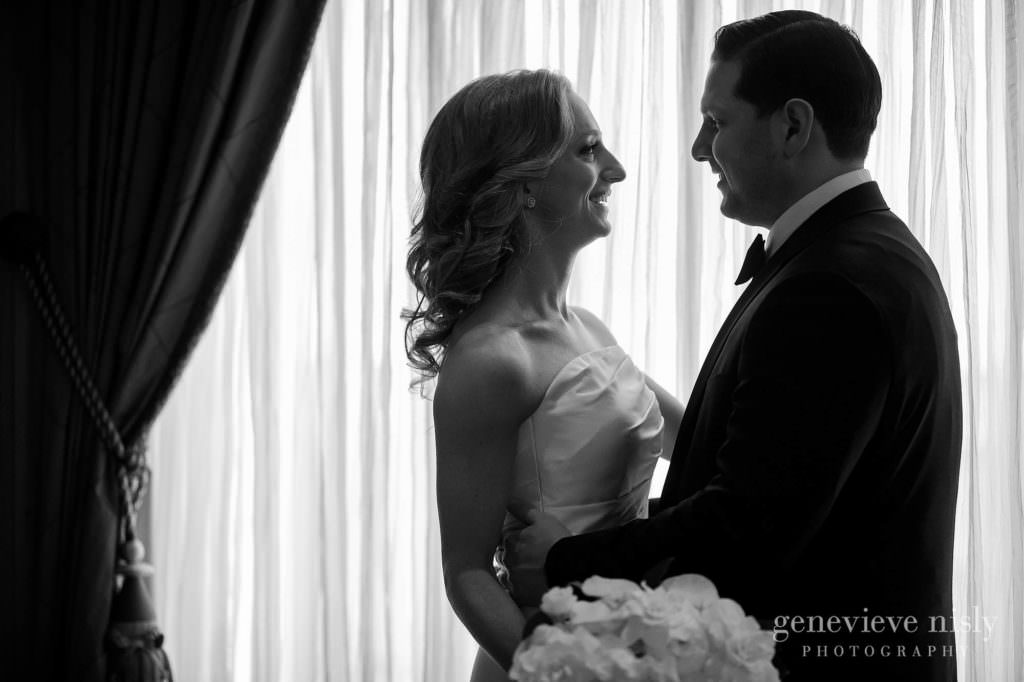 Black and white portrait of bride and groom in front of a window.