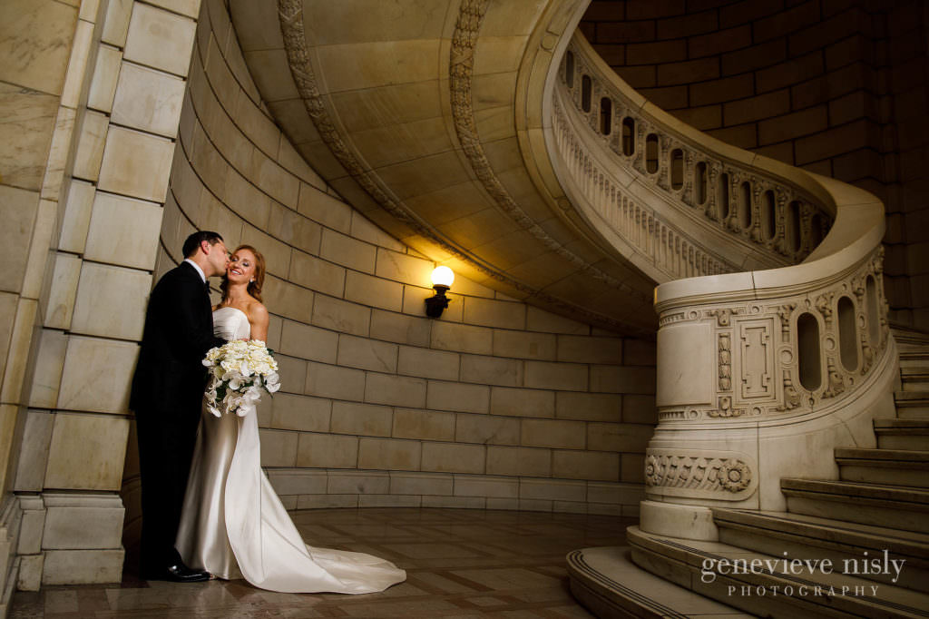 Groom kisses bride's cheek near the staircase at the old courthouse.