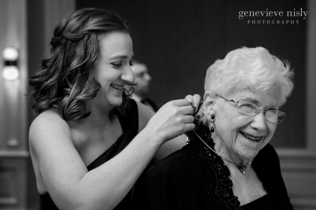 Sister helps grandma with her dress.