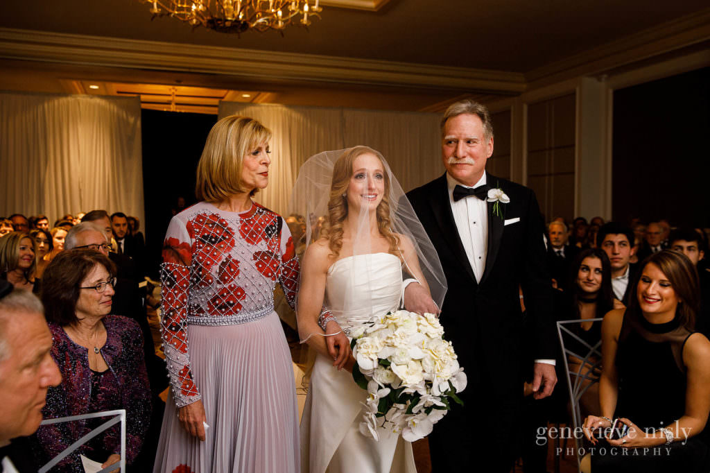 The bride walks down the aisle with her mother and father.