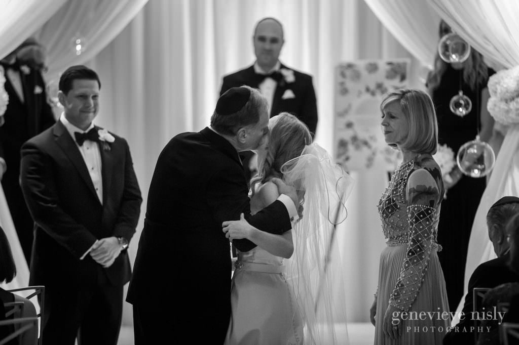 The bride's dad kisses her on the cheek during the ceremony.
