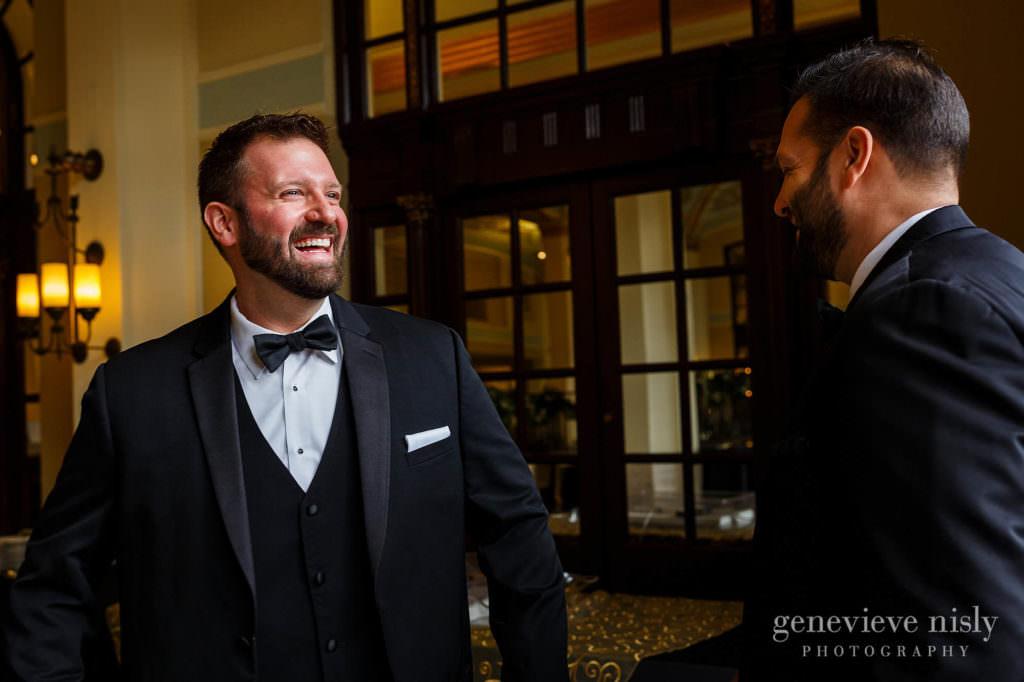 Groom smiles at his groomsman at the Onesto Lofts.