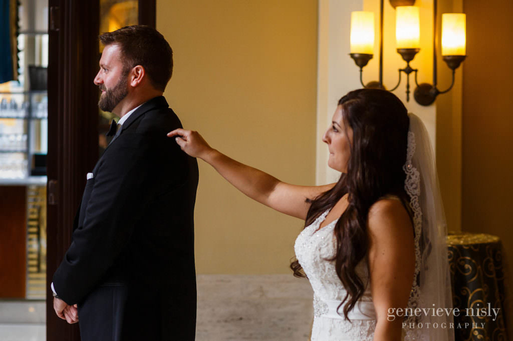 Bride taps groom on his should during their first look at their wedding at Onesto Lofts.