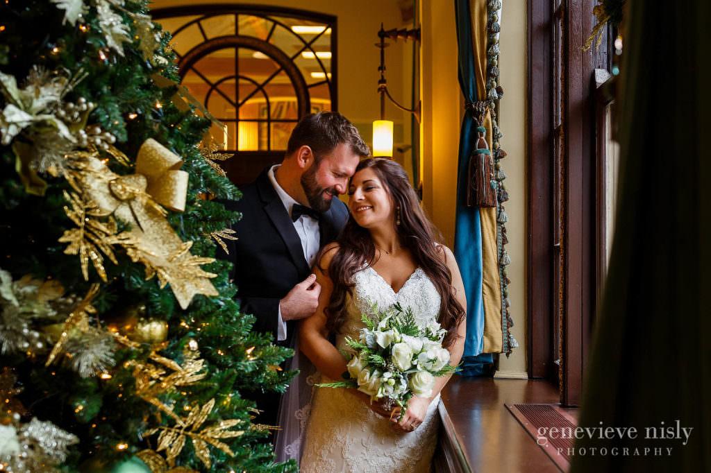 Bride and groom hug near a Christmas tree during their Onesto Lofts wedding.