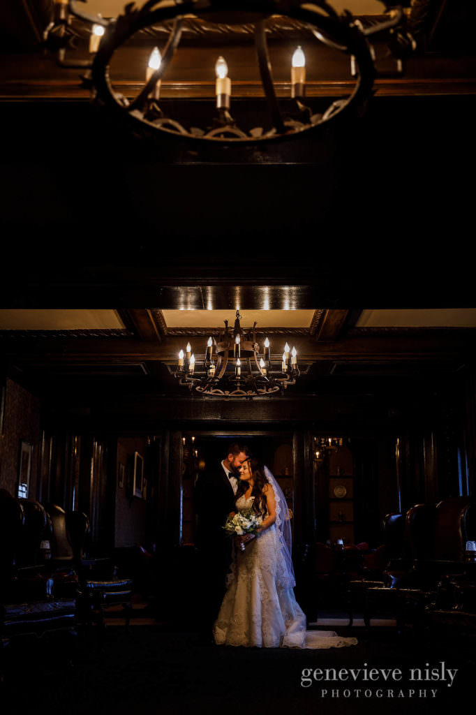 Bride and groom under the chandeliers at the Canton Club.