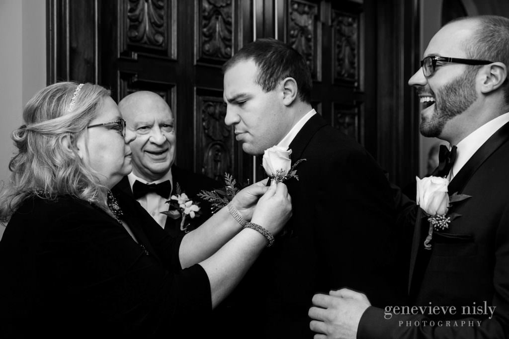 Mom helps son pin a flower on his jacket at the wedding ceremony.