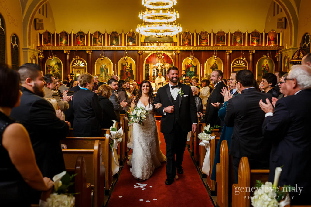 Bride and groom walk back down the aisle at the end of the wedding ceremony at St. Haralambos Church.