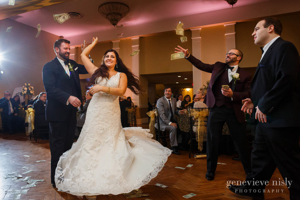 Brother tosses dollar bills on wedding couple during their first dance at the reception.