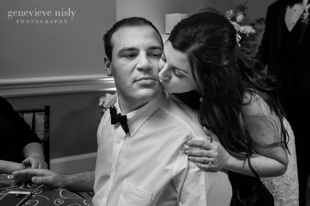 Bride kisses her brother on the cheek during the wedding reception.