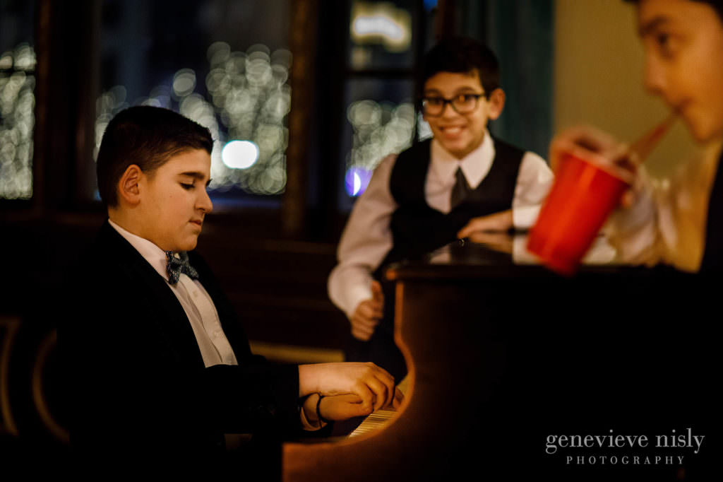 Wedding guests play the piano in the lobby of Onesto Lofts.