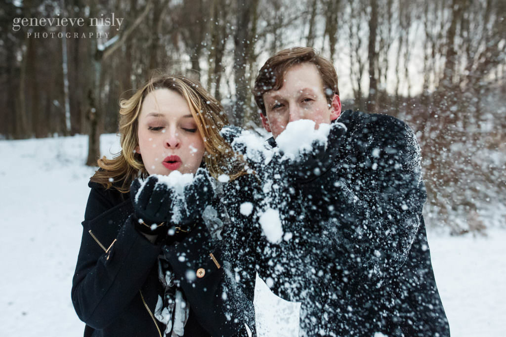 Michael and Jacee blow snow at the camera during their engagement session.