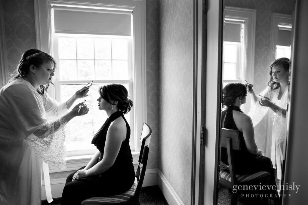 The bride applies makeup to her bridesmaid on her wedding day at Mooreland Mansion.