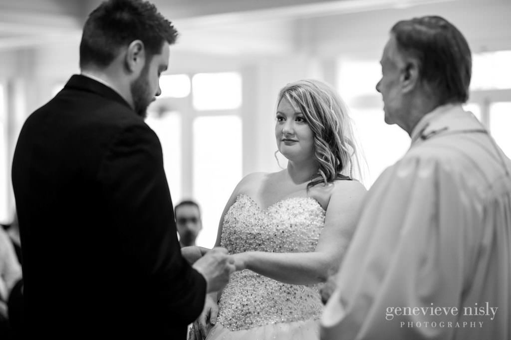 The groom places the wedding ring on his bride's finger during their Moorland Mansion wedding ceremony.