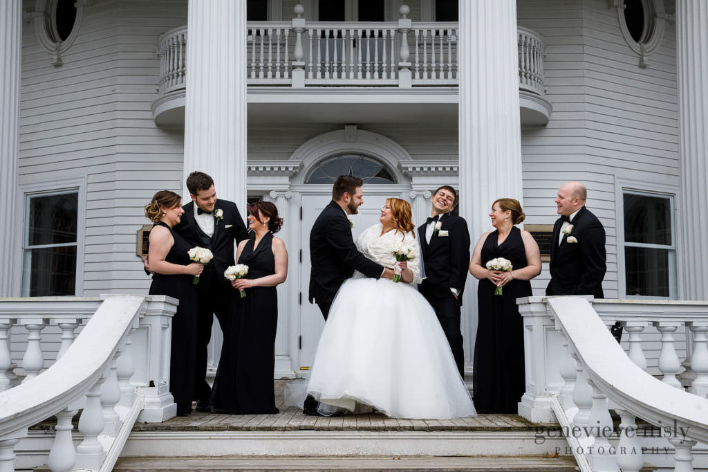The groom, bride and entire bridal party having a laugh on the steps outside the Mooreland Mansion.
