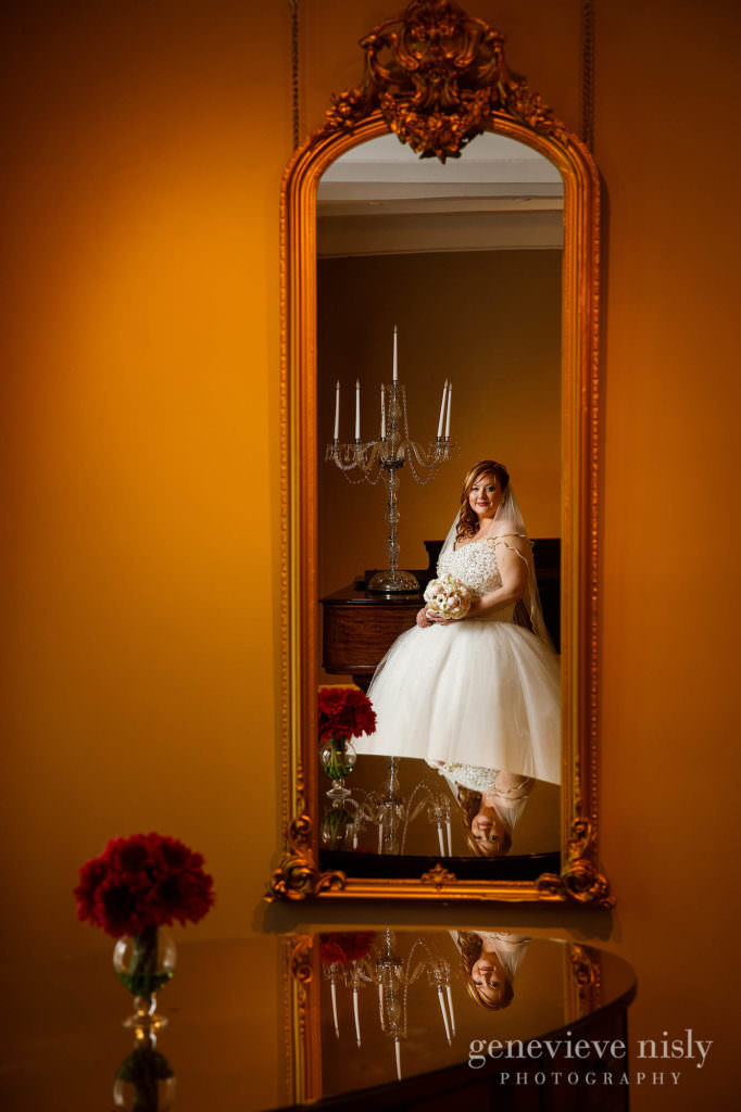 The beautiful bride is admiring her reflection at Mooreland Mansion.