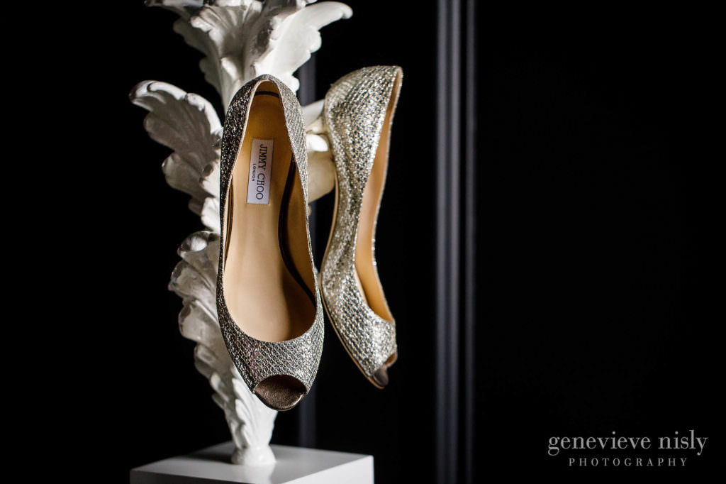 A Bride's sequined wedding shoes hanging on a lamp.