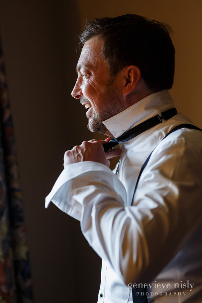 A groom adjusts his bowtie while laughing.