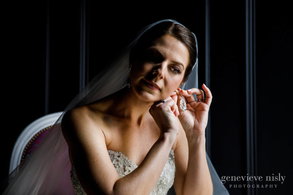 The bride putting on her earrings.