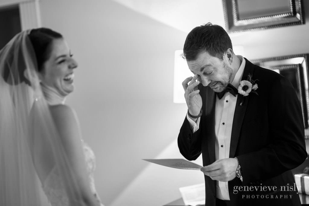 The bride laughs while the groom wipes a tear as they read letters to each other.