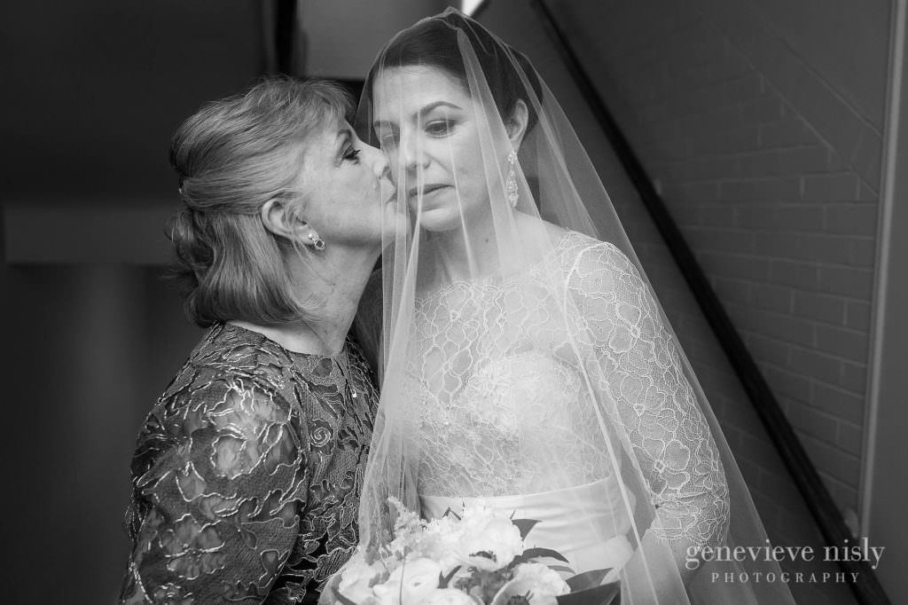 The mother of the bride kisses the bride on the cheek moments before walking down the aisle.